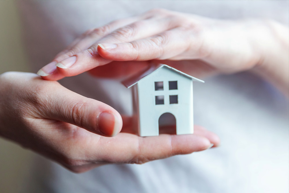Female woman hands holding small miniature white toy house