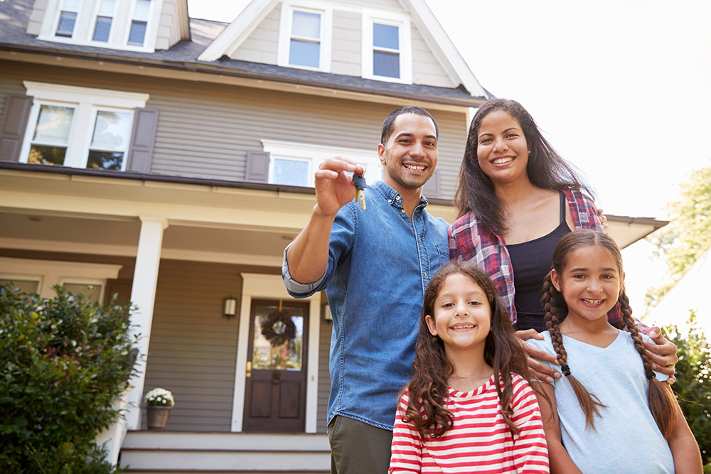 Portrait Of Hispanic Family Holding Keys To New Home On Moving In Day